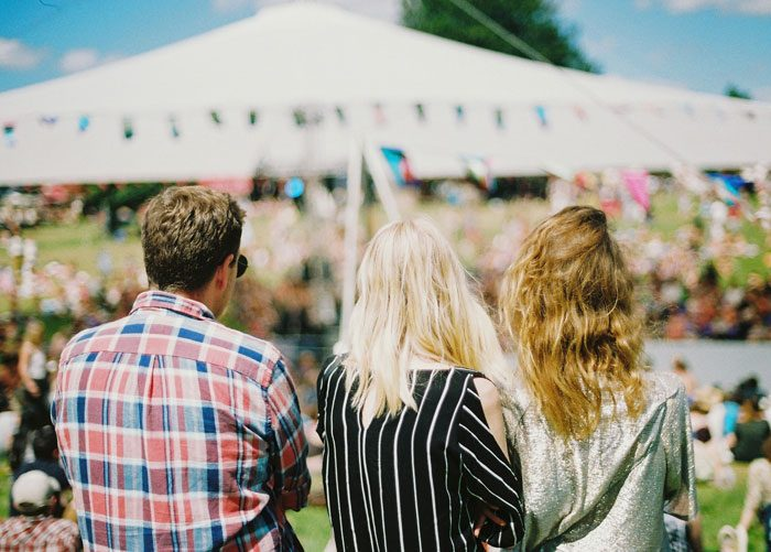 three friends attending a summer outdoor event
